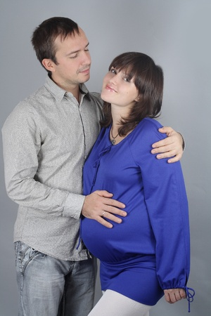The young man gently looks at the pregnant wife Stock Photo