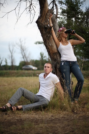 The guy sits near a tree, nearby there is a girl and looks in the field-glass