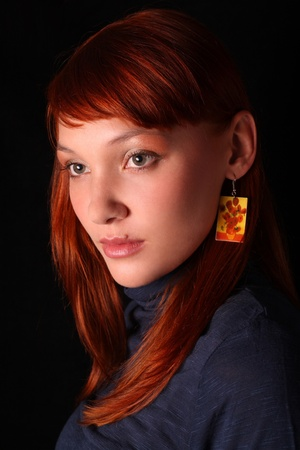 The red-haired girl looking through a shoulder on a black background Stock Photo - 8926355