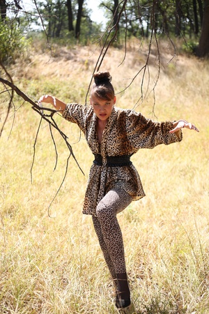The girl in a suit of a leopard against the wild nature Stock Photo - 8926497