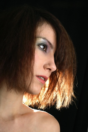 Portrait of the girl on a black background with illumination behind Stock Photo
