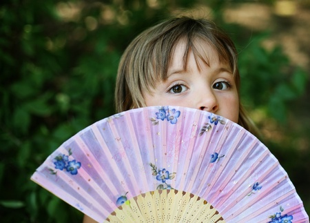 The girl has closed the face a fan
