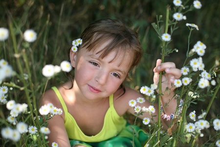 Portrait of the girl sitting in camomiles (small depth of sharpness) Stock Photo