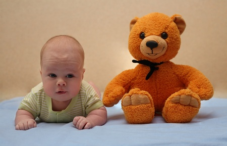 The child lying on a stomach and its teddy bear Stock Photo