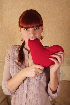 girl fuusly biting red heart Stock Photo - 8926579