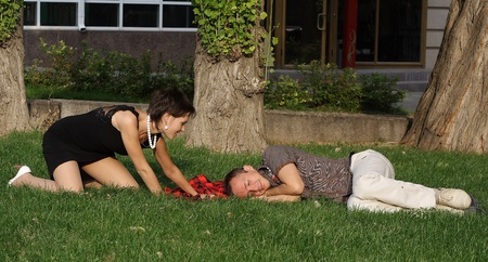 The guy and the girl have a rest in park on a grass Stock Photo