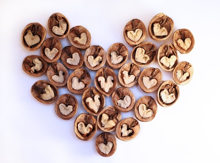Halves of walnuts are laid out in the form of heart (isolated) Stock Photo
