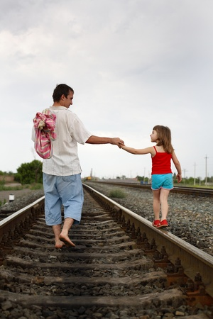 goods train: The father and daughter go having joined hands by rail Stock Photo