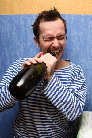 Portrait of the unshaven man, opening teeth a wine bottle