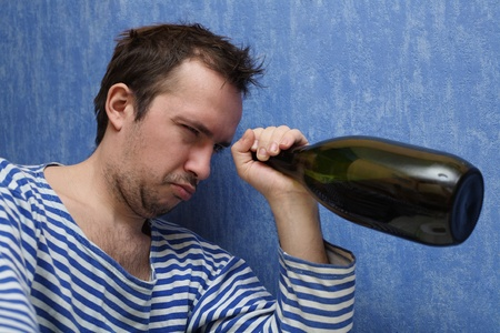 The drunkard looks in a bottle with wine Stock Photo