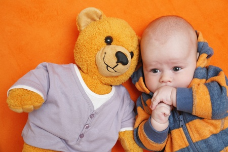 The baby lying on a back and its teddy bear Stock Photo