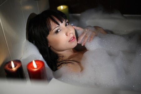 The girl lies in a bath with foam, candles burn Stock Photo - 9102406