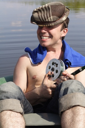 The young man sits in a boat with a spinning and smiles Stock Photo