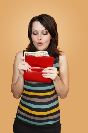 The girl holds a purse with money and surprised Stock Photo
