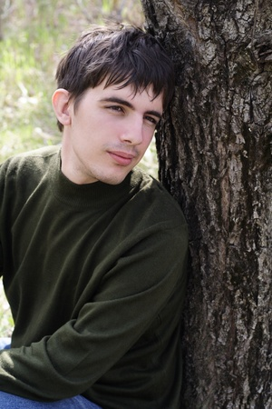 The thoughtful young man sits having leaned against a tree Stock Photo - 9266882