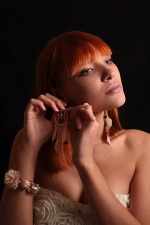 The red-haired girl tries on beautiful earrings Stock Photo - 11569308