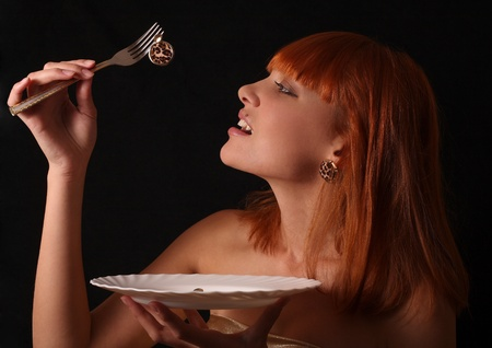 The red-haired girl has control over a plug with a gold earring and a plate Stock Photo - 11569306