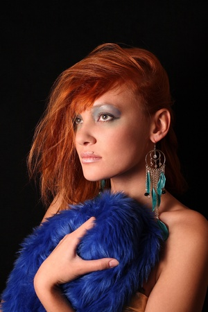 The red-haired girl with a bright make-up has control over a dark blue fur coat