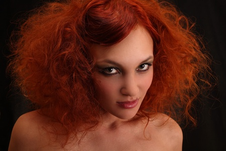 Portrait of the curly red-haired girl. On a black background. Stock Photo