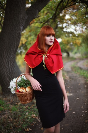 The red-haired girl with a flowers basket. On a wood footpath. photo