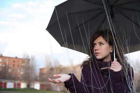 The girl under an umbrella catches rain drops. A rain from threads.
