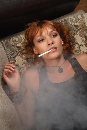 The girl sits on a sofa and  smokes photo