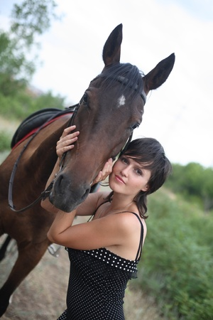 The girl costs near a stable and irons a horse Stock Photo