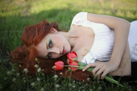 red-haired girl lying on the grass with a bouquet of flowers