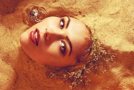 portrait of a girl surrounded by sand