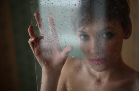 Girl behind the glass with rain drops Stock Photo