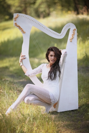 girl in white dress playing the harp white photo