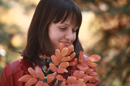 girl holding a branch of mountain ash with red leaves