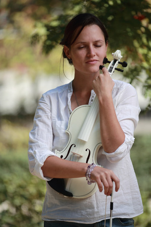 girl with violin closed her eyes and thinks