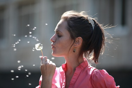 portrait of a girl blowing a dandelion
