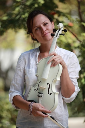 Portrait of a girl with a white violin in hands
