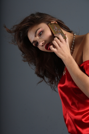 beautiful girl in a red silk dress talking on mobile phone