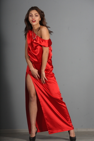 beautiful girl in a red silk dress photo