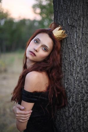 Portrait of a princess standing near a tree Stock Photo