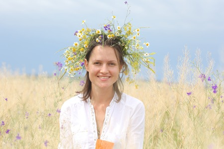 in a lush field girl with a wreath of flowers on her head