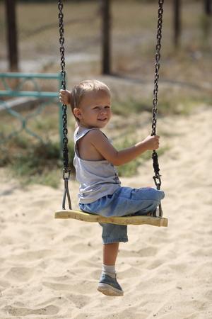 Little boy sitting on a swing, looking back Stock Photo