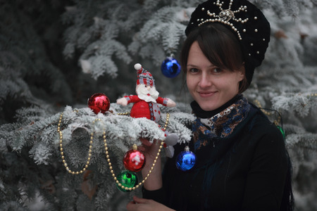 elegant girl standing next to a Christmas tree decorated with toys