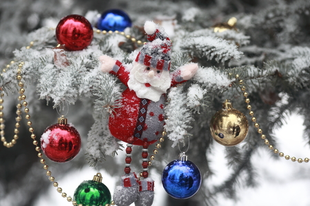 Christmas tree covered with snow and dressed toys