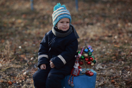 boy sitting on a stump next to the artificial Christmas tree