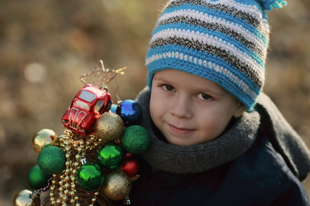 boy holding an artificial Christmas tree decorated with toys Stock Photo