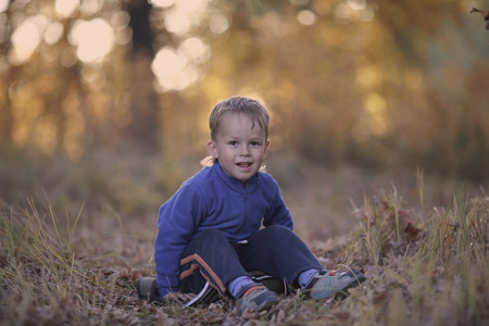 Cheerful smiling boy in a tracksuit, sitting on the grass