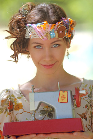girl in the crown of sewing accessories holding a sewing machine