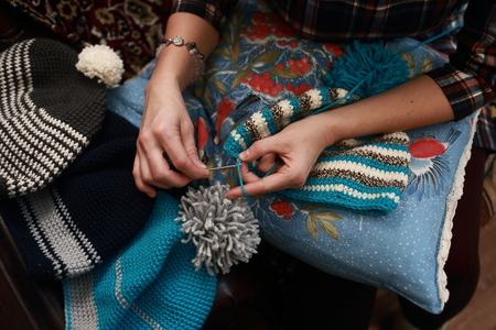 hand of a woman who crochet beanie warm of colored wool