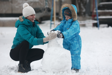 4 year old: 4 year old boy in blue overalls sculpts snowman with his mom Stock Photo