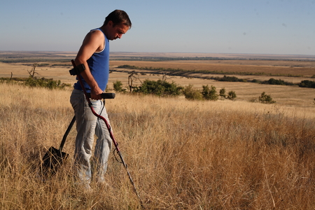 detector: archaeologist man with a metal detector in hand Stock Photo