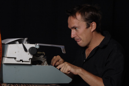 enthusiastically: male writer enthusiastically working on a typewriter, his tongue hanging out